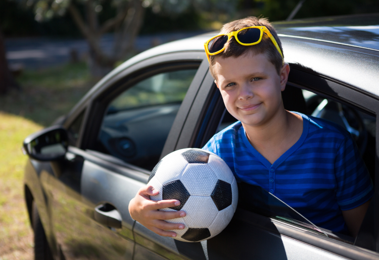 boy in car ready to play soccer