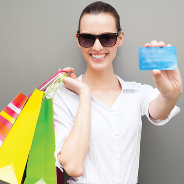 woman showing credit card and holding shopping bags